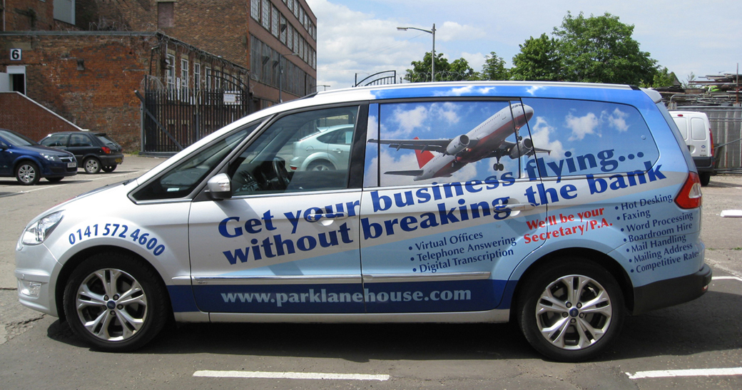 "Image shows a silver Ford Galaxy people-carrier with vehicle livery by Adamson Design. In shades of blue, the design uses an aeroplane graphic to advertise virtual office services with the slogan: ""Get your business flying… without breaking the bank."""