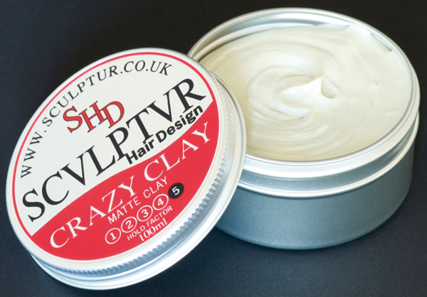 Photo shows a circular silver tin of mens hair wax opened, the wax is off-white. The lid has a bold red-and-black design called Crazy Clay, part of the Sculptur range.