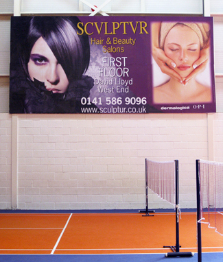 Photo shows a full-colour advertising Billboard Poster for Sculptur Hair & Beauty Salons in an indoors tennis court at David Lloyd health club in Glasgow. The poster has two portraits of models, one for hair and one for beauty treatments.