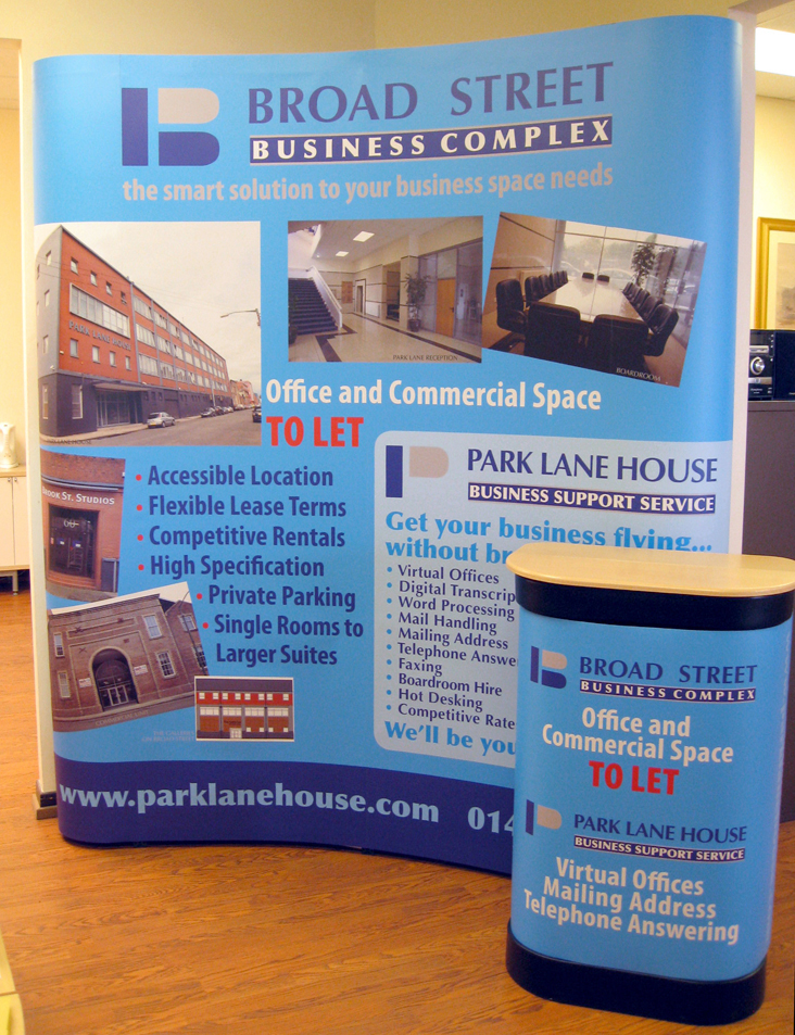 Photo shows a curved wall-type of exhibition stand for Broad Street Business Complex in Glasgow. It has a sky blue (cyan) background with exterior and interior photos of the business centre, committee room, foyer etc. In front of the curved wall is the transit case it travels in, dressed with a matching graphic wrapper and a wooden counter-top to make it a counter during the exhibition.