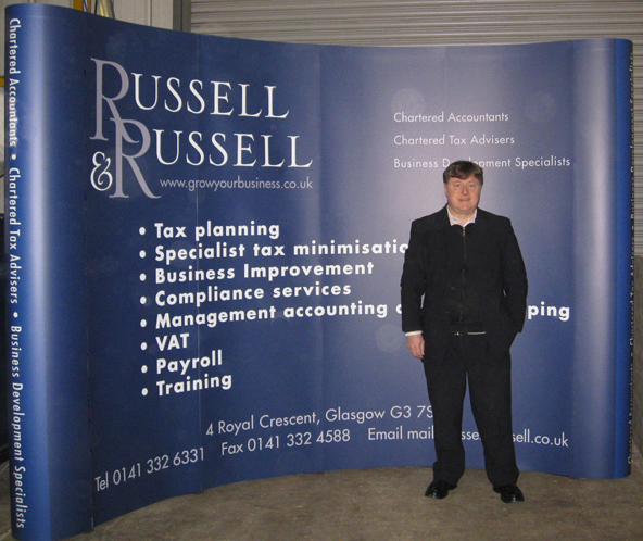 Picture shows a four-by-three size exhibition stand I designed for Russell & Russell Accountants. Wider than most exhibition stands, it's a dark blue curved wall with the R&R logo top left, white bulletpoint text in the centre and contact information along the foot. The curved endcap corners have a lighter shade of blue. I'm shown standing in front of the stand in the workshop.