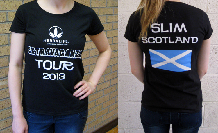 Front and back views of the Herbalife-Slim Scotland T-shirt being modelled. It is a black lady-cut T-shirt with white design showing (front) the Herbalife logo and Extravaganza Tour 2013 and (back) Slim Scotland and the Saltire, which is in white-on-blue.