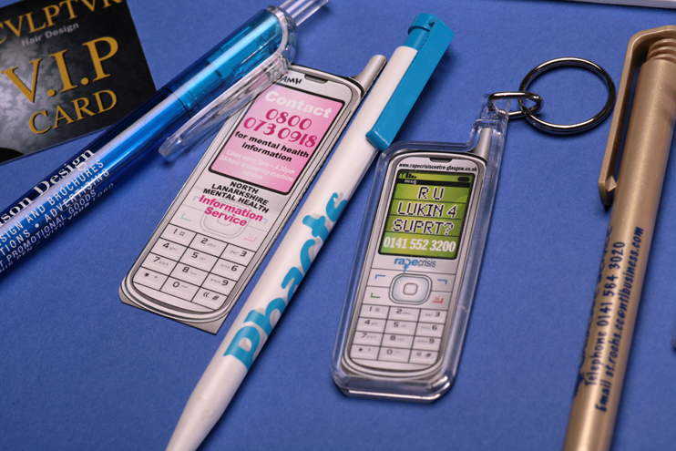 A close-up photo of Promotional Goods showing the branding details on a VIP membership card, three pens and two mobile-phone-shaped keyrings.