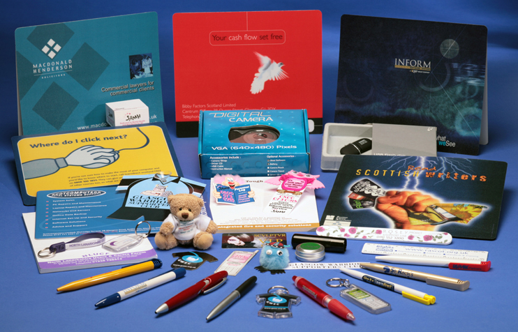Picture shows a wide range of Promotional Goods supplied by Adamson Design, including branded pens, keyrings, mousemats, pads, USB-sticks and camera. The brightly-coloured gifts are shown on a blue tabletop.