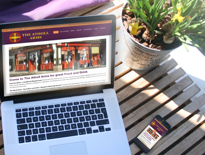 "Mockup photo of ""The Atholl Arms"" Website on MacBook Pro and iPhone on a café table."