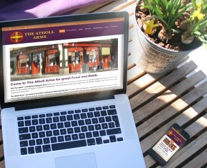"Mockup photo of ""The Atholl Arms"" website design on MacBook Pro and iPhone on a café table."
