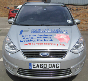 "Front view of vehicle wrap graphics on a silver Ford Galaxy. This view shows the bonnet with text, logo and a broken-piggybank image symbolising ""without breaking the bank"", all promoting a business support service in Glasgow."