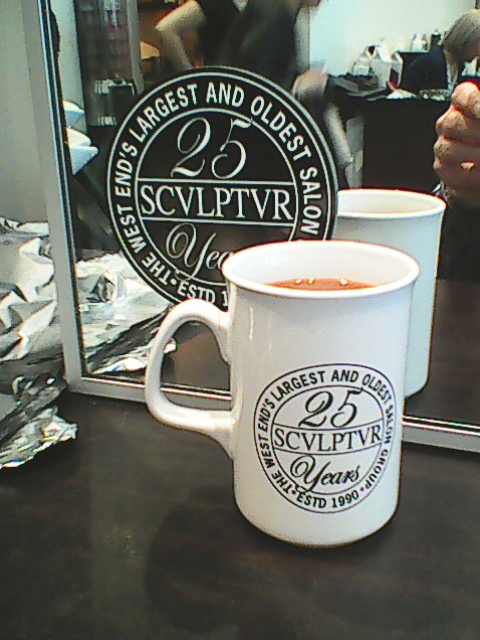 Picture shows a white mug branded with the black-white Sculptur 25 Years Logo in front of one of the mirrors in the hair salon, which is similarly branded with a logo-sticker.