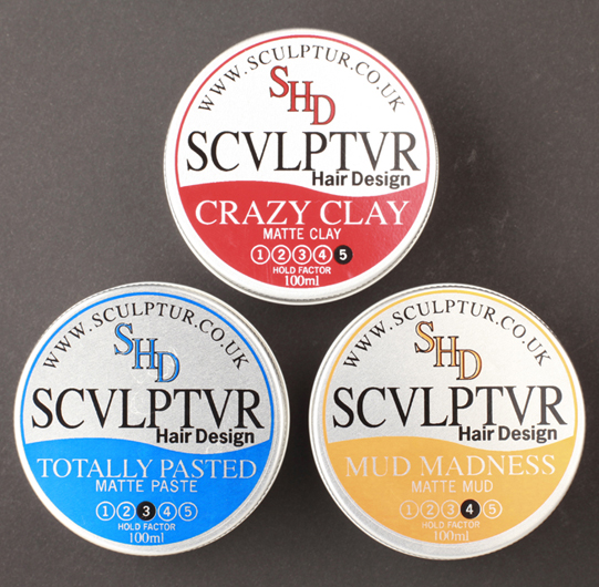 Pic of Mens Hair Wax Tins – called Crazy Clay, Totally Pasted and Mud Madness – designed for Sculptur Hair, Glasgow by Adamson Design. The lower half of the round silver tins are printed Red for Crazy Clay, Royal Blue for Totally Pasted and Yellow Ochre for Mud Madness in a soft wave shape.