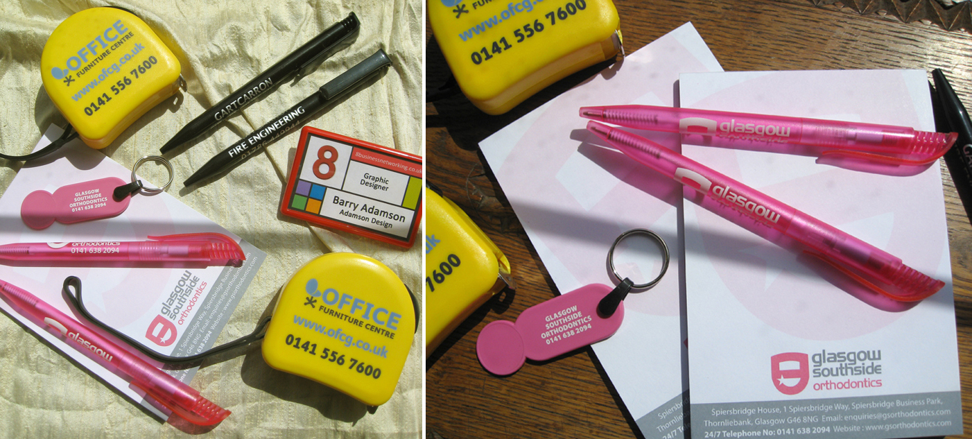 Picture shows a variety of Promotional Goods branded with clients' logos and details, including pens, notepads, badges, trolley coin key rings and tape measures.