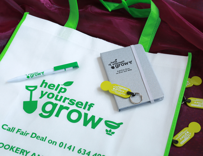 Close-up of promotional goods branded for the Help Yourself Grow project, consisting of tote-bag, pen, notebook with silver cover and trolley-coin key rings.