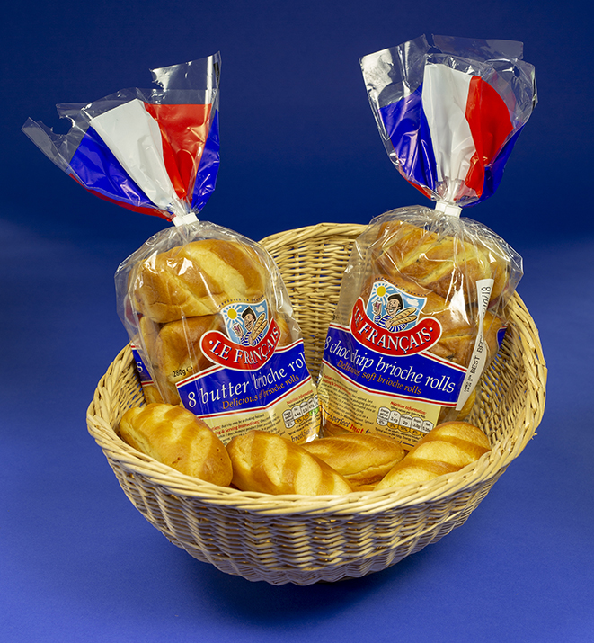 The photo shows two packs of French Brioche Rolls in their transparent packaging, sitting in a wicker basket. The packs are branded LE FRANCAIS and are decorated in red, white and blue, with the 'tail' of each pack simulating the French flag. There are two types of pack – Butter Brioche and Choc-Chip.