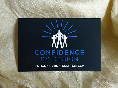 The picture is of a black business card which features the new brand identity for Confidence by Design.