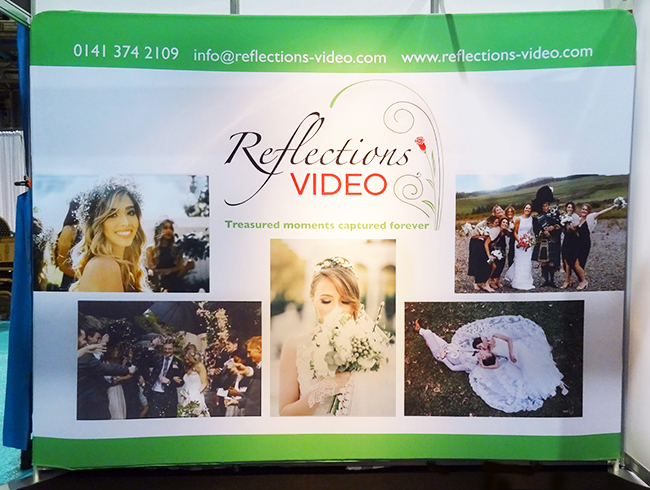 "Exhibition stand design: photo of an exhibition stand of the ""fabric wall"" type, a colourful fabric background stretched over a tubular aluminium frame. This one was designed for Reflections Video (wedding videos)."
