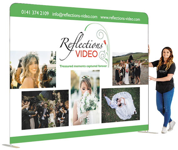Picture shows a straight wall exhibition stand, 2.3 high x 3 metres wide with a girl standing beside it to show scale. The graphics on it are wedding photos for Reflections Video, wedding videographers.