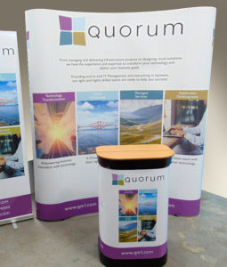 Pic shows a curved wall exhibition stand for Quorum, Edinburgh, with its transit case set up as a counter in front of it. Logo colours are purple, pale blue, teal and ochre with purple on white background for the panels.